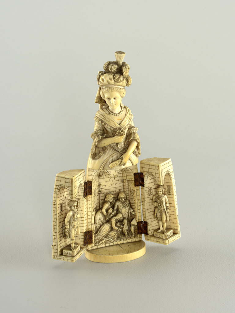 Carved ivory figure of Marie Antoinette depicted in court dress; her skirt opens to for a triptych. The center panel shows the royal family in prison. The wings show Georges Jacques Danton (1759 – 1794) and Honoré Gabriel Riqueti, Count of Mirabeau (1749 – 1791).