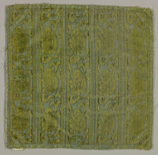 vertical stripes of scrolls in green. Selvage present.