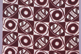 Square of printed cotton with twisted fringe on two warp ends. Checkerboard design in dark reddish-brown and tan with brown crackle effect. The lighter squares contain a brown ring in an irregular square; the brown squares contain a shield-like form. Strings of beads run throughout the design.
