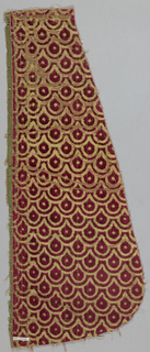 Gold background with all-over repeat of imbricated tear-drop or scale motif in red velvet. The pieces are shaped as if they were once part of a chausable.