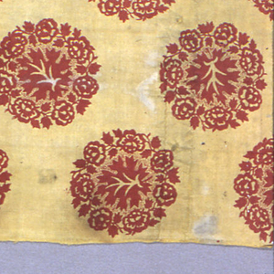 """Mustard yellow ground, printed in detached circular design of flower wreath framing leaf, in bright red. Design arranged in staggered rows, each element about 3 3/4"""" across. Printing appears to be by block, superimposed on the yellow ground. Picotage around leaf. Both selvages present. Pieces of yellow 2/2 twill fabric used on the pieced side as part of the border."""
