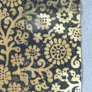 Fragment of heavy hand-woven linen in a dark cream color block printed in black. Design is mostly reserved in background color with details in black. Curving vine and stylized flowers forming an allover pattern. Block mark shows across center of piece.