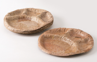 Package of ten circular, stacked plates of brown dried leaves stitched with grass twine; each plate molded with three sections and rounded rim.
