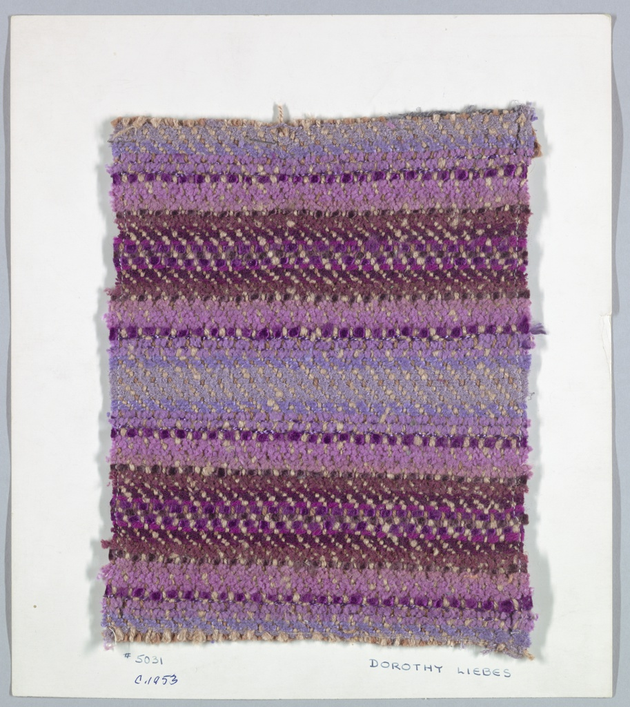 """1/3 twill with a variety of wefts, predominantly deep purple.  Warp: 1 brown 3 ply yarn, 3 beige 2 ply yarn.  Weft: bands of various yarns making 4 3/4"""" repeat. Yarns include chenilles, smooth yarns and plied yarns in varying weights all in purple or maroon."""