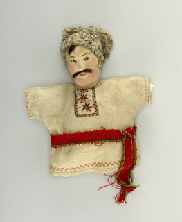 Head of a stockinet with painted face, real hair and fur cap; clothed in short smock of linen with cross stich decoration and a red and green sash.