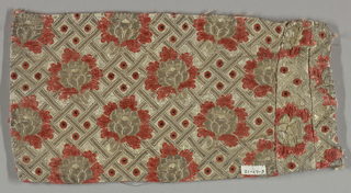 Flower brocaded in thick rust colored chenille thread and silk on a background trellis pattern in metallic threads.