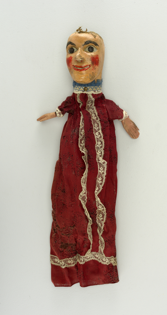 Wide-eyed face with red cheeks. Figure dressed in red and white lace, blue fringe at the neck. Remains of crepe hair.