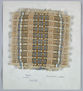 Sample with warp stripes of unpaired and grouped yarns including chenille, flat metallic braid, metallic braid over a central core and shiny synthetic. Left side is mirror image of right side. Weft has large round reed followed by three narrow round reeds.