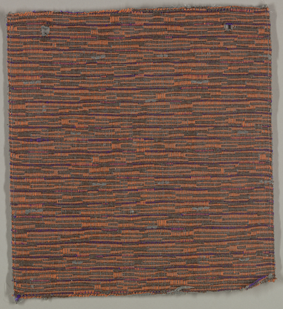 Sample of hand woven cotton in which the warps are much thinner and more tightly twisted than the loosely-twisted, slubby wefts. The wefts are grouped in combinations which vary across the width of the fabric, giving a meandering, rather than strictly grid-like, appearance. Brown and orange warps; slate blue and purple wefts.