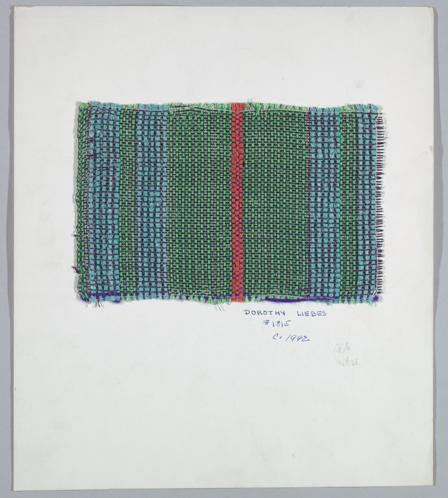 Woven sample mounted on cardboard card with notations by the designer. Vertical stripes of blue and green with a narrow red stripe in the middle. Warp is plied synthetic yarns in blue alternating with fine purple metallic yarns, green alternating with fine green metallic yarns, and red plied synthetic yarn. Weft alternates very fine purple and green metallic yarns. Selvedge on left side.