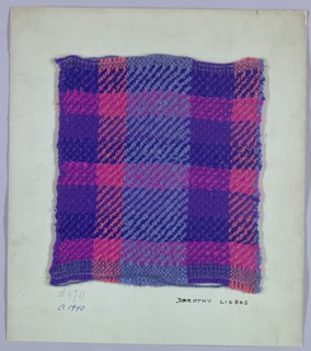 Woven sample mounted to a cardboard card with notations by the designer. Twill plaid in shades of purple, blue, coral and bright pink. Warp has bands of purple and blue synthetic two-ply yarns and coral bouclé. Weft has bands of bright pink, blue and purple synthetic yarns in a repeating sequence. A few rows of plain weave at top and bottom; selvedges on left and right sides.