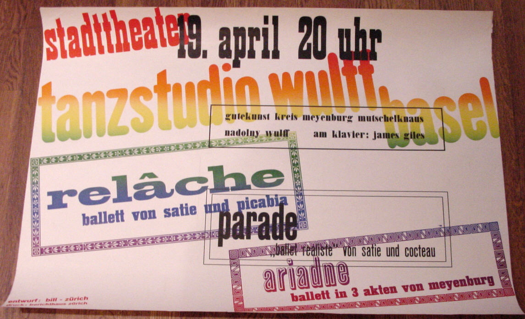"""A mixture of different type fonts arranged on a diagonal opposition with rectilinear text blocks. Printed in """"split-fountain"""" which produces color transitions from red at top left, through orange, yellow to green, blue, lavender and violet at bottom right corner. The date is printed in black at top center."""
