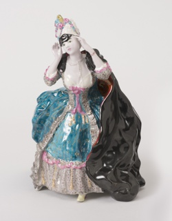 A lady dressed in fancy 18th-century style ball gown, with hands lifted to black mask on face.