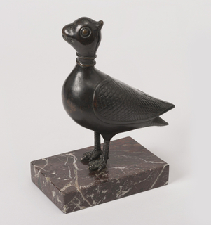 Stylized bronze figure of a standing bird on rectangular white-veined brown marble plinth.