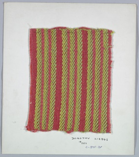 Woven sample mounted to a cardboard card with notations by the designer. Horizonal stripes of green and red. Warps alternate two shades of red two-ply cotton. Weft is bands of red bouclé in plain weave, two shades of green plied yarn in 2/2 twill, and red smooth yarn in 1/3 twill. Selvedges at left and right sides.