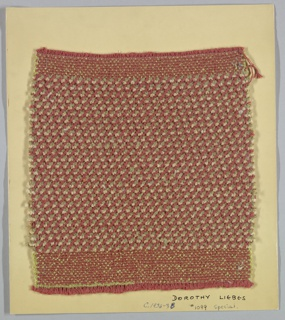 Woven sample mounted to a cardboard card with notations by the designer. Overall tweed effect. Warp is of four-ply, copper-colored cotton yarn. Weft is a repeating sequence of light and dark gray chenille and copper-colored metallic cable of 2 strands of 6 wrapped elements twisted together. Bands of plain weave with paired warps and green boucle wefts at top and bottom.