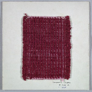 Woven sample mounted to a cardboard card with notations by the designer. Dark red with very fine pink horizontal stripes. Warp alternates two thick and two thin dark red cotton yarns; weft is pink three-ply cotton.