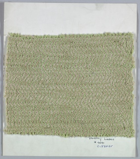 Woven sample mounted on a cardboard card with notations by the designer. Vertical herringbone twill in green and gray. Warp is green bouclé; weft is grey chenille paired with grey bouclé. Selvage on right side.
