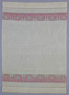 Small white table mat with a design in pink on either border.