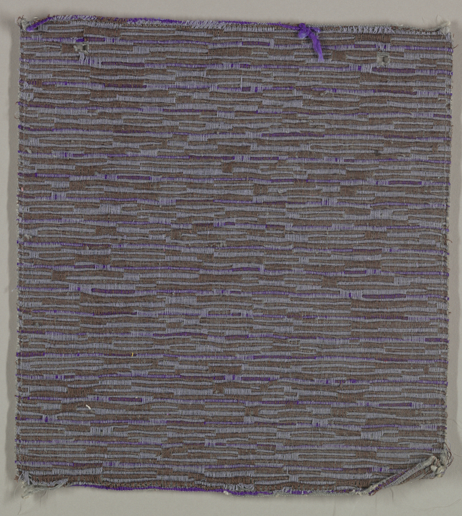 Sample of hand woven cotton in which the warps are much thinner and more tightly twisted than the loosely-twisted, slubby wefts. The wefts are grouped in combinations which vary across the width of the fabric, giving a meandering, rather than strictly grid-like, appearance. Brown and slate blue warps; slate blue and purple wefts.