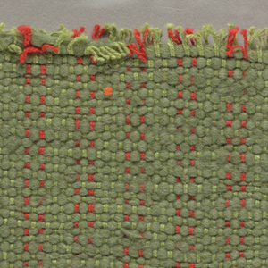 Sample of hand-woven cotton in which the warps are much thinner and more tightly twisted than the loosely-twisted, irregularly spun wefts, which vary in thickness across their length. Red-orange and green warps; green wefts.