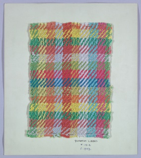 Woven sample mounted to a cardboard card with notations by the designer. Balanced plaid in bright colors. Warp has stripes of green, two shades of yellow, two shades of orange, three shades of blue, and pink boucle. Weft has bands of nine different yarns, glossy, chenille, boucle and paired. Selvedge on left side.