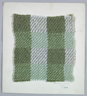 Woven sample mounted to a cardboard card with notations by the designer. Twill plaid in two shades of green, pale blue and silver. Warps are even stripes of green bouclé and light blue yarn. Weft has bands of green bouclé and flat silver metallic strip, wrapped silver metallic yarn, and braided clear plastic strips. Selvage at left side.