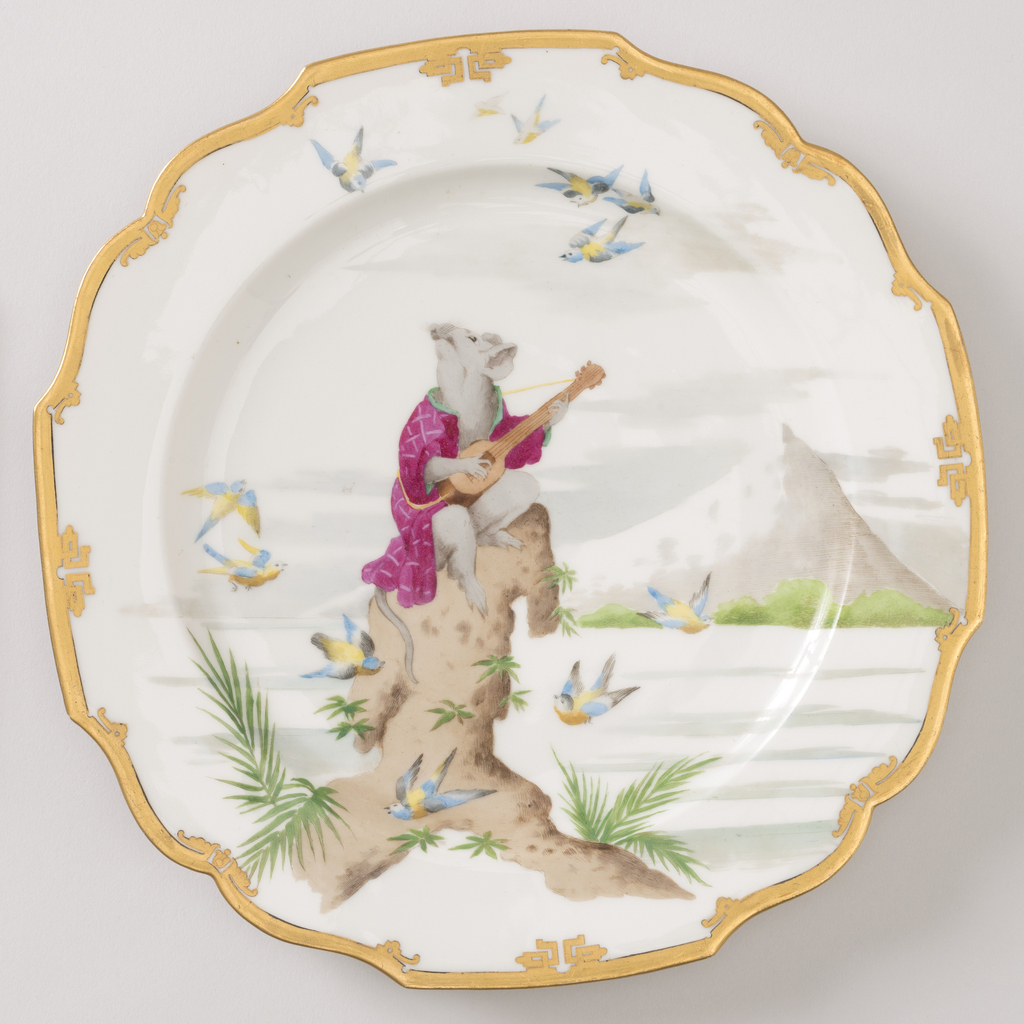 A white plate with a gold lip depicting a mouse sitting on a tree stump, playing the guitar with a mountain in the background.