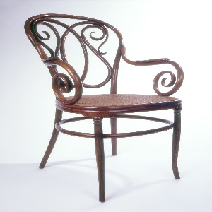 """Bentwood armchair with caned seat, two scrolling armrests, circular """"stretcher"""" and four tapered legs.  Armrests on each side terminate in scrolls."""