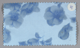 Light blue ground has an allover pattern of apple blossoms in shades of dark and light blue.