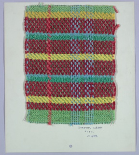 Woven sample mounted to a cardboard card with notations by the designer. Twill plaid in red, yellow, green and blue with metallic accents. Warp has stripes of six-ply green cotton alternating with green wrapped metallic yarn, two-ply turquoise alternating with with purple wrapped metallic yarn, and two-ply red yarn. Weft has bands of red, loosely twisted yarn alternating with red wrapped metallic yarn, green bouclé, yellow two-ply, and blue two-ply. Bands of plain weave at top and bottom.