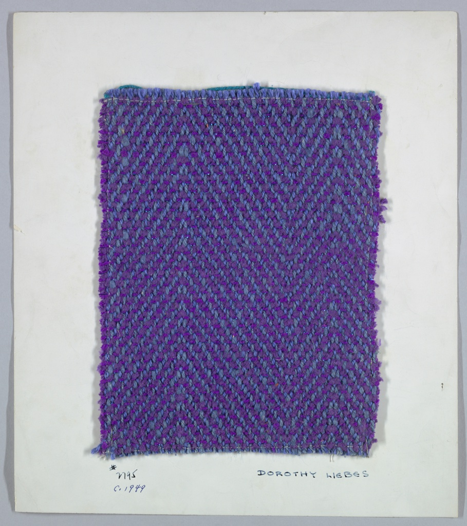 Symmetrical 2/2 horizontal herringbone twill in shades of blue and purple. Warp is two-ply blue yarns that alternate. Weft is purple chenille that alternates with two-ply purple yarn combined with narrow synthetic blue metallic yarn.