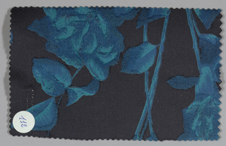 Black ground has an allover pattern of blue roses with blue leaves and stems.
