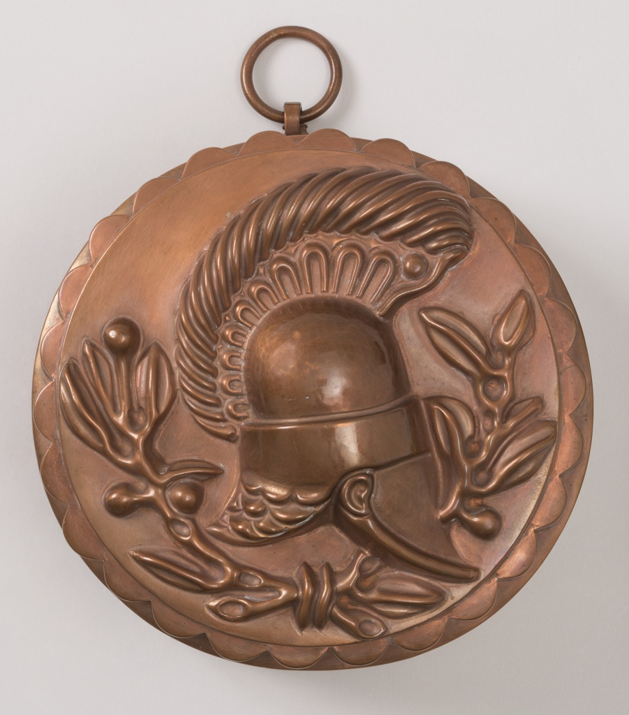 Decorated on bottom with repoussé trophy composed of helmet of laurel; on sides, with repoussé hemicylinders.