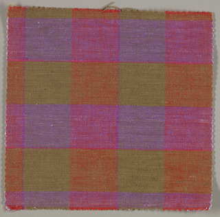 Sample of a hand woven cotton plaid with a slightly slubbed texture. Warp has wide bands of orange and olive; weft has wide bands of olive and purple with narrow stripes of bright pink.