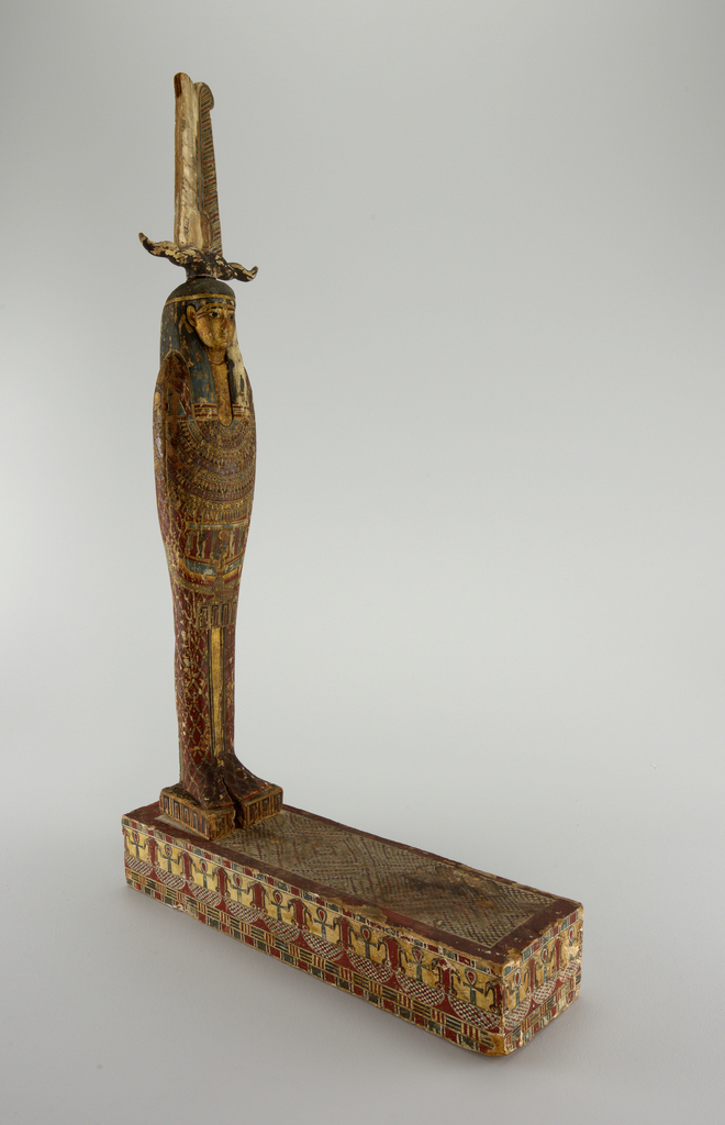 Figure with feathered headdress and gilt face standing on a square block, fitted with peg. Patterend surface of body. Long rectangular base with ahnks.