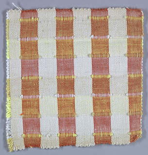 Sample of hand-woven cotton in which the warps are thinner and more tightly twisted than the loosely-twisted, slubby wefts. Wide stripes in each direction are interrupted occasionally with very narrow ones of 2 warps or wefts each. The vertical stripes are accented with insertions of discontinuous weft which is very thick and raised. Orange and ivory warps; light and dark yellow wefts and brocading yarns.