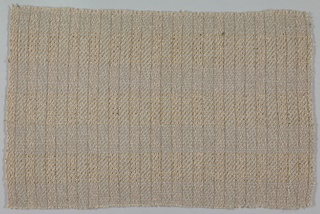 Delicate plaid formed by various novelty wool yarns in shades of grey and beige combined with gold and silver flat strips wound on a silk core.