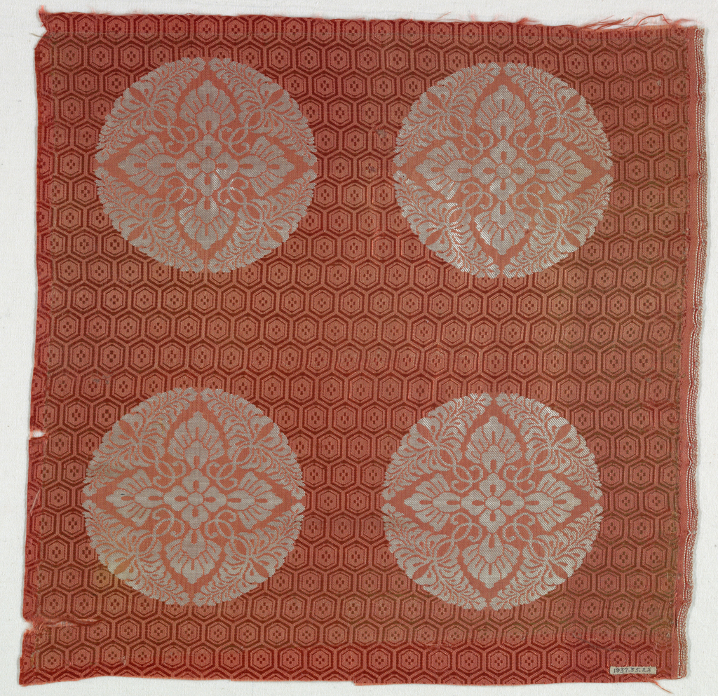 Orange ground with a hexagonal diaper pattern. Four quatrefoil foliate design forming circles and brocaded in white silk.