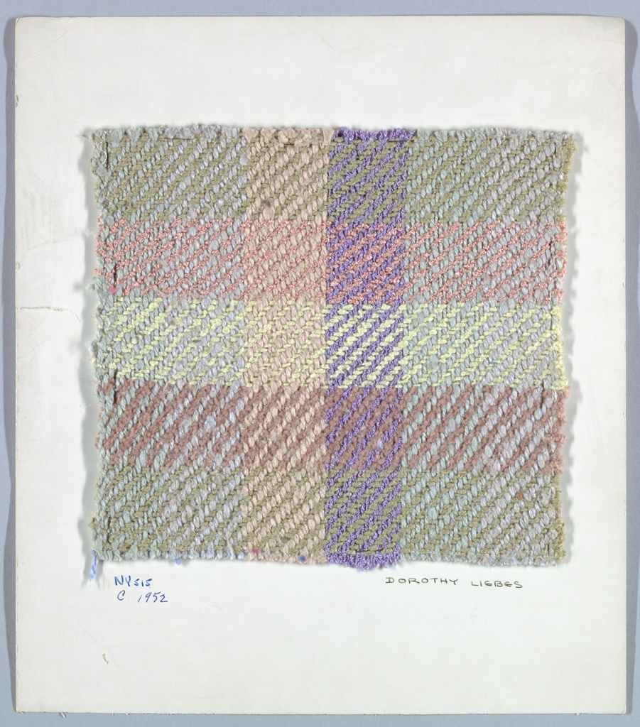 2/2 twill plaid in muted colors. Warp has stripes of light blue, light gray, light brown two-ply yarn, light purple boucle. Weft has bands of green plied, brown chenille, yellow plied and pink boucle yarn.