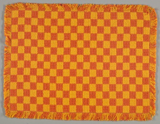 Four fringed placemats woven in an allover checkerboard effect in orange and golden yellow. Yellow blocks are plain weave, orange blocks are a huck lace construction. Four plain orange napkins complete the set.
