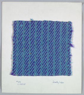 Woven sample mounted to a cardboard card with notations by the designer. Warp is a sequence of eight purple two-ply yarns in two different thicknesses, alternating with four metallic gold wrapped yarns. Weft is turquoise cotton chenille.