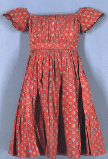 Child's short-sleeved dress in a red printed floral cotton.