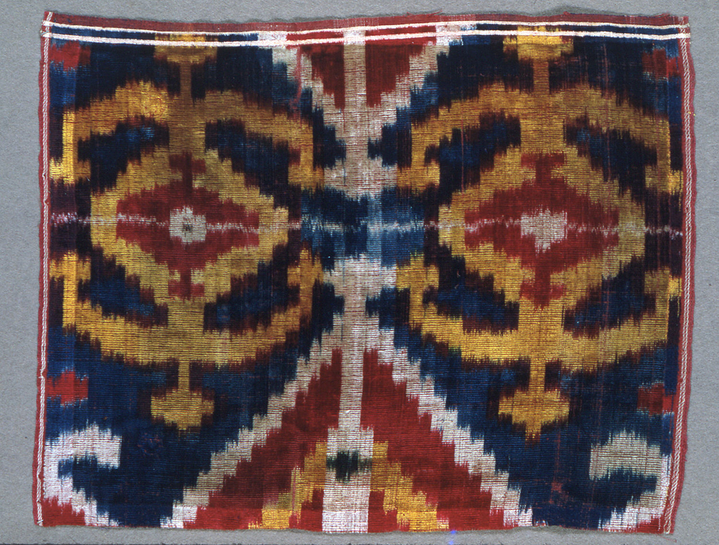 Scaled and blurred medium-scale geometric design in crimson, gold, rust, white, and green on ground in shades of deep blue. Two crimson twill selvedges with paired white pencil stripes.