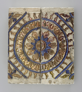 Tile decorated with brown and blue floral motif, bordered by two blue concentric circles; winged foliate in corners.