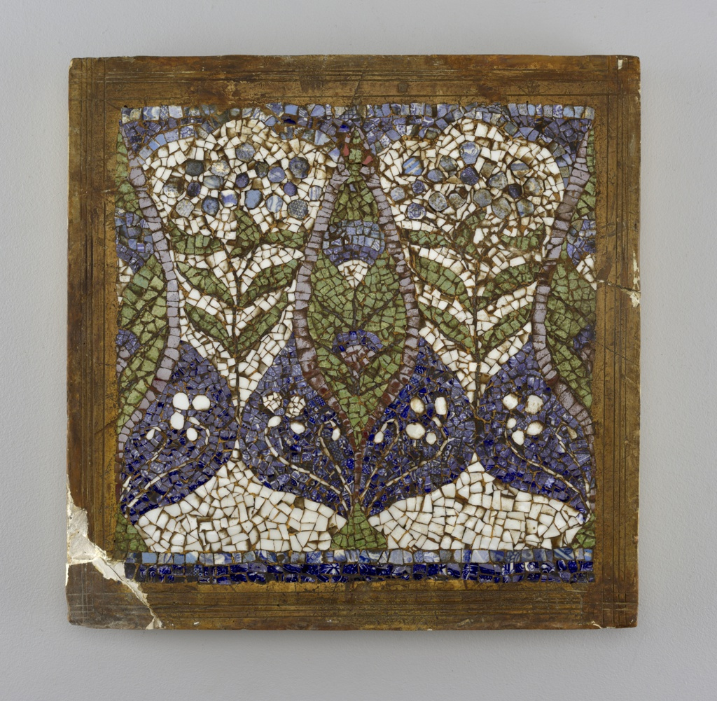 Square plaque composed of irregular glazed ceramic fragments set in and framed with plaster; mosaic.  One complete and two halves of repeating design of vertical green leaf in bulb-shaped blue field at base.  Leaf, bulb and white ground contain flowers in opposing colors.