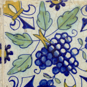 Two tiles each of a similar design, in blue, green and neutral yellow, with fleurs-de-lis at four corners, leaves and two small bunches of grapes; in center of tiles a and b, a pomegranate, of tiles c and d, a large bunch of grapes.