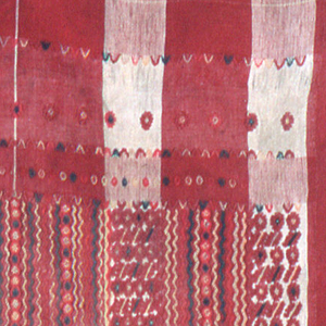 Square with large plaid in shades of red and white with large central panel of close-set zigzags, stripes and small geometrical figures in shades of bright pink, green, lavender, white and red. Widely spaced narrow side stripes of animals, rosettes and scales.