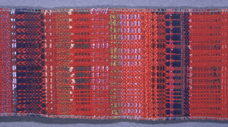A rich, subtle plaid of varied colors and textures, created by using many different yarns in the warp. In shades of red, brown, blue, purple, pink, gold and green, with red predominating.