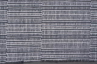 Broad vertical stripes composed of various black and white check effects, formed by a single set of variously combined black and white warps and wefts.